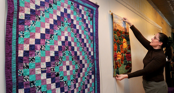 Amesbury:<br /> Jennifer Rogers arranges quilts made by artist Leah Allman for this weekend's show at Wick'd Kool in downtown Amesbury.<br /> Photo by Bryan Eaton/Newburyport Daily News Wednesday, April 01, 2009