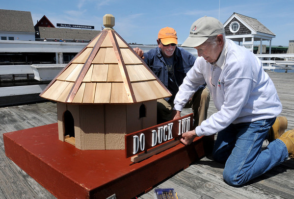 "Newburyport:<br /> A new inn is coming to the waterfront, but this inn is not for people, it's for ducks. Charles ""Pete"" Morse built this duck house and is attaching the sign as Windward Yacht Yard manager Butch Frangipane watched. The house, which replaces one lost in a storm last year, will be put in the water between Michael's Harborside and the yacht yard to keep ducks off the docks.<br /> Photo by Bryan Eaton/Newburyport Daily News Friday, April 24, 2009"