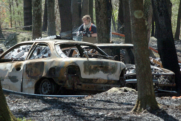 Georgetown: A firefighter sprays down some hot spots of a brush fire that damaged these automobiles on Parish Road in Georgetown on Tuesday afternoon. Bryan Eaton/Staff Photo  Newburyport News  Tuesday April 28, 2009.