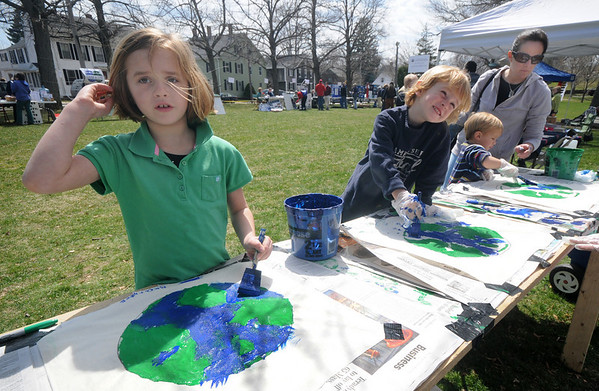 Newburyport: Bea Rogers, 6, along with her brothers Tripp 3, Jude, 2, and their mom Heather from North Andover paint canvas earth posters with Girl Scout troop 60617 at the Earth Day celebration on the Bartlett Mall Saturday. Jim Vaiknoras/Staff photo