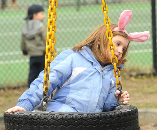 Newburyport:Celia Celona, 7, rides the tire swing at the Newburyport Mothers' Club Easter egg hunt at Perkin's Park. Jim Vaiknoras/Staff photo