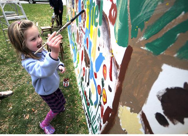 Newburyport: Caroline Walsh, 6, of Newburyport, puts her mark on a large mural at the Earth Day celebration on the Bartlett Mall Saturday. Jim Vaiknoras/Staff photo