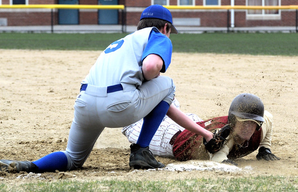 Georgetown: Newburyport High's Kyle McElroy gets a face full of dirt as he dives safrly back to first  under the tag of Georgetown's Michael Ruh during their game at Georgetown Saturday. Jim Vaiknoras/staff photo