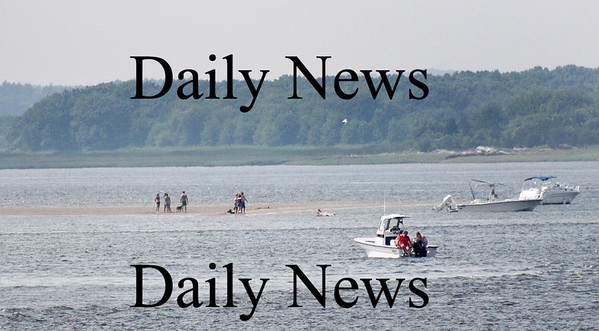 Newburyport: A small crowd gathers on the sand bar near the mouth of the Merrimack River off of Plum Island Monday afternoon. Photo by Ben Laing/Staff Photo