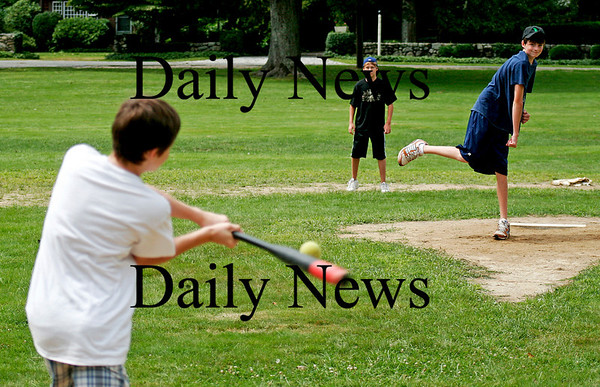 Newbury: Devin Shuman, 13, of Newburyport, takes a swing on a pitch from john Brennan, 13, of Newbury. Will Koski, 13, also of Newbury, stands at second base as they group played ball at the Upper Green in Newbury Monday afternoon. Photo by Ben Laing/Staff Photo