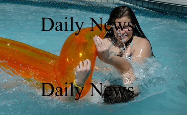 Salisbury: Samantha Pike, 12, dumps neighbor Cameron Smallidge, 14, in his family pool as they and some of his cousins cool off from the heat. Showers may come through tonight, but the weekend looks clear with the weather becoming less humid. Bryan Eaton/Staff Photo  Newburyport News August 19, 2009.