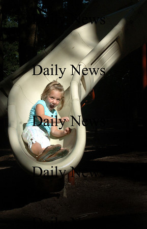 Newburyport: Paige Cohen, 5, yells with glee heading down one of the slides at Moseley Woods as she spends some last days as a pre-schooler.<br /> The Georgetown girl, there with her parent David and Jessica, starts kindergarten next week.  Bryan Eaton/Staff Photo Newburyport News Thursday August 27, 2009.