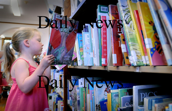 Amesbury: Chili Dowd, 4, chooses some books to take home from the Children's Room at the Amesbury Public Library on Wednesday. She had come in to drop off some other books and pick up her certificate for the number of books she read during the summer reading program. Bryan Eaton/Staff Photo  Newburyport News August 19, 2009.