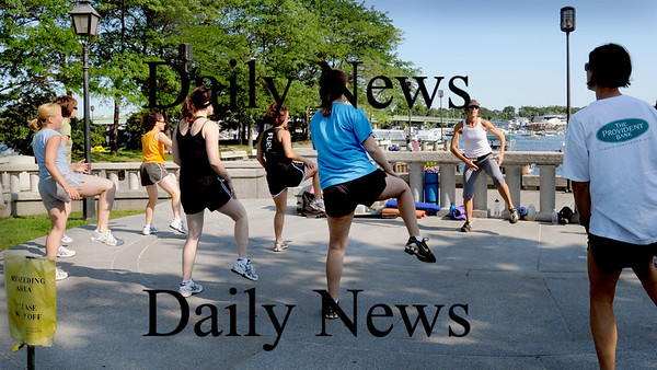 """Newburyport: Jeanne Carter of Fuel Training Studio leads her """"boot camp"""" on the stage area at Waterfront Park yesterday morning. Bryan Eaton/Staff Photo Newburyport News  Friday August 7, 2009."""