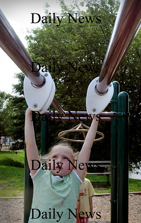 Newburyport: Zoe Seese, 5, moves along the moving monkey bars in the playground across from the Kelley School in Newburyport. She was with the Summer Youth Program which headed outside for some playground fun after snack time.  Bryan Eaton/Staff Photo Newburyport News Wednesday August 5, 2009.