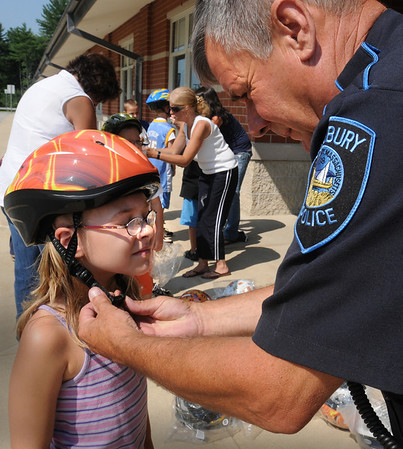 Salisbury: Salisbury police officer Mike Alder adjusts Jessica Hood's bicycle helmet that the eight year-old received along with other younsters at Salisbury Elementary School's Kid's Club  Summer Program. Alder, the school resource officer, brought the helments, which the department donated, and gave some bicycle safety tips.  Bryan Eaton/Staff Photo Newburyport News  Monday August 3, 2009.
