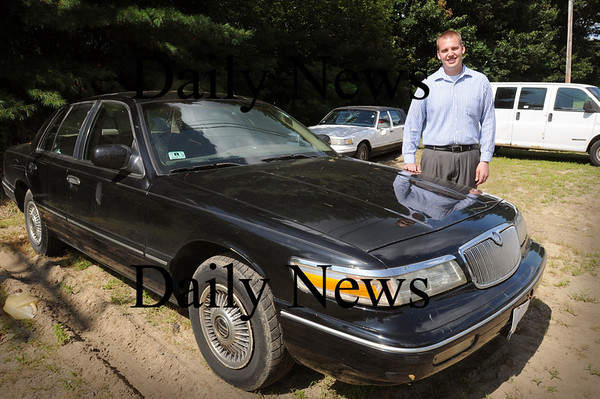 "Salisbury: John Wall, Jr. of Wall's Ford in Salisbury with three ""clunkers""  destined for the scrapyard. Bryan Eaton/Staff Photo Newburyport News  Friday August 7, 2009."