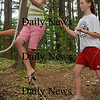 Amesbury: Castine Bernardy, 14, walks along a wire rope as she's spotted by Julia Schlich, 12, on Tuesday afternoon. They were on the challenge course at Camp Kent in Amesbury in one of the summer programs there.  Bryan Eaton/Staff Photo  Tuesday August 11, 2009.
