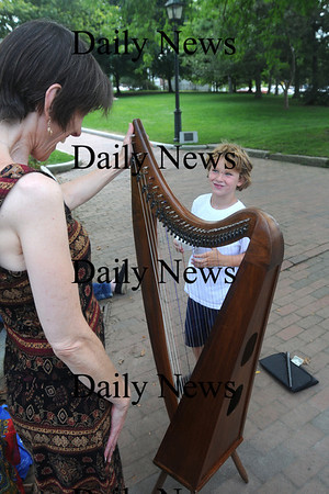 Newburyport: Moiri Kelly of Georgetown shows her harp to Andrew Gilligan, 7, in Waterfront Park Thursday. Moiri was playing and singing when Andrew stopped to listen then ask questions about the instument. Jim Vaiknoras/Staff photo