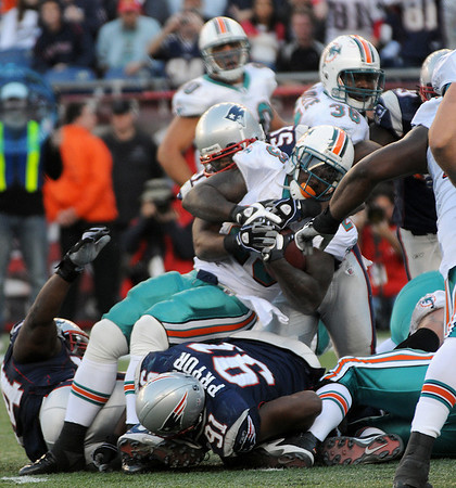 Foxboro: Miami running back Ronnie Brown (23) gets stopped at the line of scrimmage by Jerod Mayo (51) and Myron Pryor (91). Photo by Ben Laing/Staff Photo