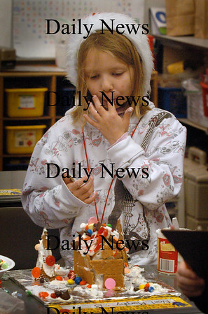 Salisbury: Noel Murphy, 7, licks some frosting off her fingers while making a gingerbread house at Salisbury Elementary School on Friday morning. The second-graders made the tasty math projects while tallying the numbers of different candies they used and creating a graph of the amounts used. Bryan Eaton/Staff Photo