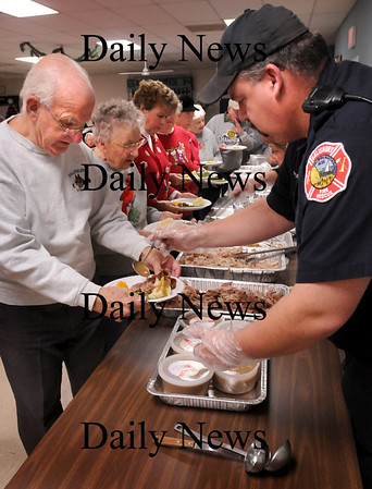 Salisbury: Salisbury firefighter David Doyle ladles gravy onto Friends of the Council on Aging member, Bob Morley's turker dinner at a Holiday Feast at the Hilton Center in Salisbury on Wednesday. Salisbury Police and Firefighters along with some family members cooked and dished up the feast for the town's senior citizens. Bryan Eaton/Staff Photo