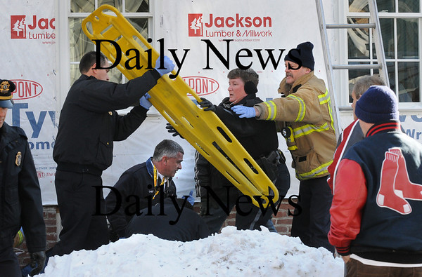 Newburyport: Newburyport Police and Fire Departments attend to one of two contruction builders who fell from a home under renovation at 27 Kent Street in Newburyport early yesterday afternoon. Bryan Eaton/Staff Photo