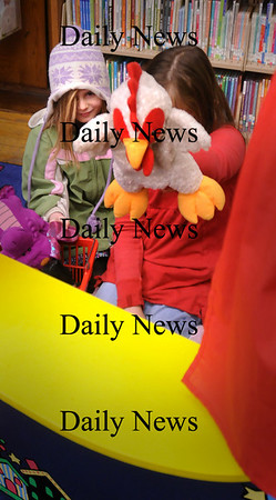 Amesbury: Chloe Davis, 7, smiles as her sister Abby, 10, goofs with a duck puppet Monday afternoon while in the children's room at the Amesbury Public Library. Bryan Eaton/Staff Photo