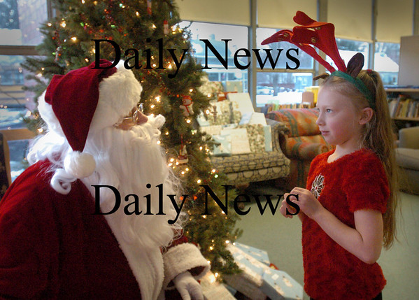 Salisbury: Lexi Cunha, 7, thinks a second as Santa Claus asks her what she'd like for Christmas while making a stop at the Boys and Girls Club in Salisbury this week. Santa gave each child a gift and presented a $1,000 check to the club from the Newburyport Bank with whom he has a close association. Bryan Eaton/Staff Photo