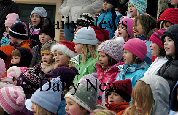 """Amesbury: Students from Amesbury Elementary School  sing """"Jingle Bells""""  in the amphitheater at the Upper Millyard on Monday afternoon. About 100 family members came out to hear the student's annual event. Bryan Eaton/Staff Photo"""
