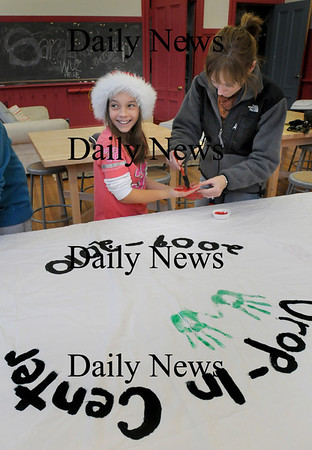 Newburyport: Michelle Thiabault, 11, gets her hands painted by Beth Manning, coordinator of the Kelley School Drop-In Center on Monday afternoon. The children there are making a mural with all their handprints to celebrate the first year of the afterschool spot for kids. Bryan Eaton/Staff Photo