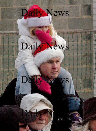 Amesbury: Caitlyn Creps, 3, covers her face from the wind while sitting on her dad, David's shoulders, in Amesbury's Upper Millyard. Her sister Madelyn, 7, and the other students from Amesbury Elementary School were in the amphitheater singing carols Monday afternoon. Bryan Eaton/Staff Photo