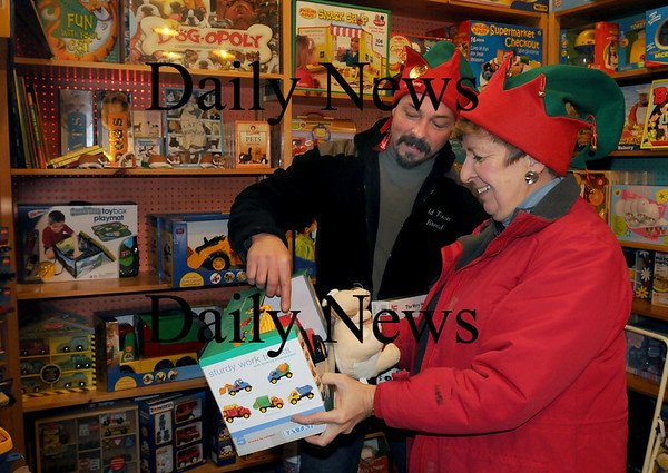 """Newburyport: Christmas """"elves"""" Doug Morris, left, and Claudette Novak buy toys at Eureka at the Tannery on Monday for their respective charities  they support, Morris' the Santa's Helper Program in Salisbury and Novak's Amesbury Holiday Program. Both are members of the Sea Spray Garden Club which is planning a garden tour in June to help support the programs, but are still taking donations for now. Bryan Eaton/Staff Photo"""