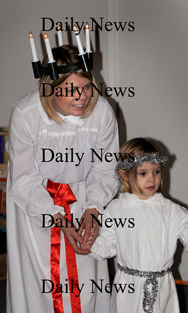 Newburyport: Tina Rawson Woodger, with daughter, Kajsa Woodger, 5, tell the story of St. Lucia, an Italian saint that was adopted by the Swedes, at the Newburyport Montessori School on Friday where Kajsa is a student. Tradionally the eldest daughter in the family dressed as the Saint, with a wreath and candles on her head, and handed out sweets to their parents and other members of the family. Bryan Eaton/Staff Photo