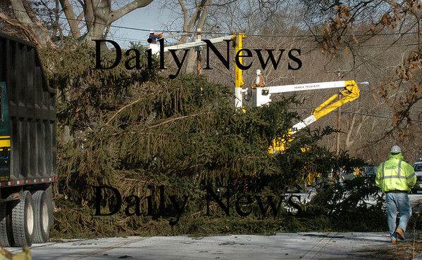 Newbury: The top half of a large evergreen snapped in the high winds and fell onto Route 1A in Newbury just north of the Lower Green late yesterday morning pulling down some electrical wires. Highway crews and a tree company had to wait until a utility crew, pictured top, cut the power. Traffic was diverted from Hay Street to Newman Road. Bryan Eaton/Staff Photo
