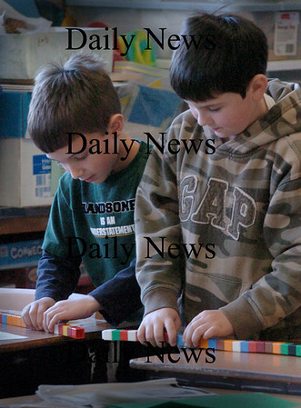Newburyport: Ben Ayotte, 6, left, and Ethan DuBois, 7, take apart stackable cubes to use in a math-related game similar to tic-tac-toe. The first-graders are in Susan Harrington's class at the Bresnahan School in Newburport. Bryan Eaton/Staff Photo