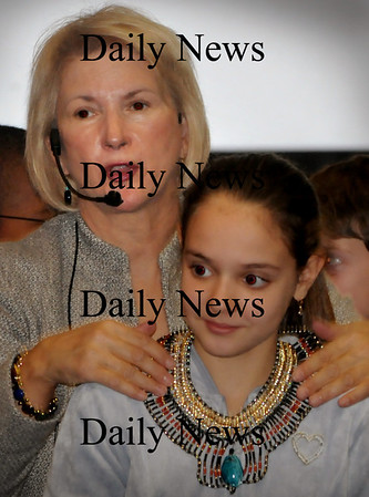 Amesbury: Paulette Morin puts a replica of an Egytian necklace onto  Sebastiana Redford, 11, at the Amesbury Middle School on Thursday morning. Morin brought her presentation with artifacts and a slideshow of ancient Egypt to the sixth-graders.