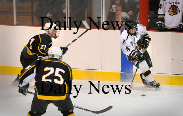 Haverhill: Pentucket's Ryan McCarthy moves the puck past North Reading's Thomas Potter (21) and Nicholas Moscaritolo. Bryan Eaton/Staff Photo