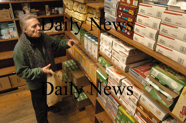 Amesbury: Don Souther fills up a bag for those in need from the food pantry at the Community Action Council at the Amesbury Town Hall Annex. Bryan Eaton/Staff Photo