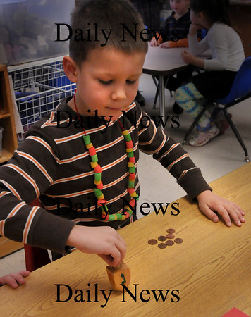Amesbury: Kindergartner Jacob Therrien, 6, spins a dreidel in Susan Gonthier's class at Amesbury Elementary School on Wednesday morning. Children were taught by a Jewish family at the school about their traditions during Hannukah, which begins Friday. Bryan Eaton/Staff Photo