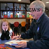 Newburyport: Lilly Brigham, 6, of St. Albans, Vermont listens to her grandfather, Frank Keslof of Plum Island, read one of several books at the Newburyport Public Library Children's Room on Tuesday afternoon. She was hoping to hit the snow with a new sled she got for Christmas while visiting, but nature wasn't cooperating, so they went to the library instead. Bryan Eaton/Staff Photo