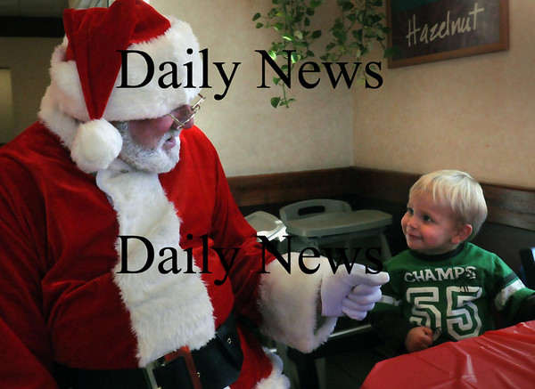 Amesbury: Santa Claus, a.k.a. Francis Cote of Amesbury, chats with Benjamin Berg, 2, of Amesbury at the Amesbury Dunkin' Donuts. Cote is part of a group of a dozen people who gather there on Friday mornings who thought Cote, with his natural white beard, would be a good Santa Claus for any children who may stop in. Bryan Eaton/Staff Photo
