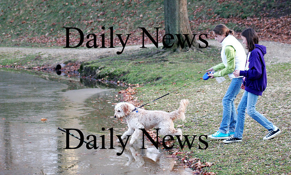 Newburyport: Schatzi, a golden-doodle, heads out on the ice at the Mall to retrieve a stick while out for a walk with Lily Eagan, left, and Eliza Filipancic, right, both 12. Photo by Ben Laing/Staff Photo