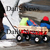 Amesbury: A youngster is bundled up tightly as he rides home in a wagon full of Christmas presents through the Upper Millyard in Amesbury Tuesday afternoon. Photo by Ben Laing/Staff Photo