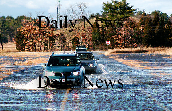 Newbury: Cars drive through a few inches of water along Newman Road in Newbury, as the abnormally high tide caused flooding in the marsh near the Little River.  Photo by Ben Laing/Staff Photo