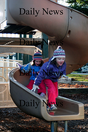 Newburyport: Twin sisters, Julia, right, and Andrea Potvin, left, of Newburyport, play on the slide at Ayers playground in Newburyport Tuesday afternoon. Photo by Ben Laing/Staff Photo