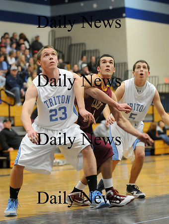 Byfield: Newburyport's Jack Nagle (12) fights for a rebound with Triton's Mike Foley (23) and Tom Bashaw (5) during Tuesday night's game in Byfield. Photo by Ben Laing/Staff Photo