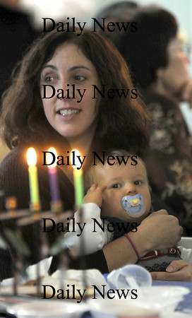 Newburyport: Beth Pfefferle holds her 10 month old son Liam Barry as the candles from the manorah burns at the annual Chanukah breakfast at the Congregation Ahavas Achim in Newburyport. Jim Vaiknoras/Staff photo