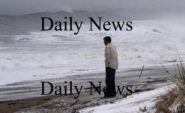Newbury: Adam Gustafson of Lowell checks out the high surf on Plum Island Sunday morning. Jim Vaiknoras/STaff photo