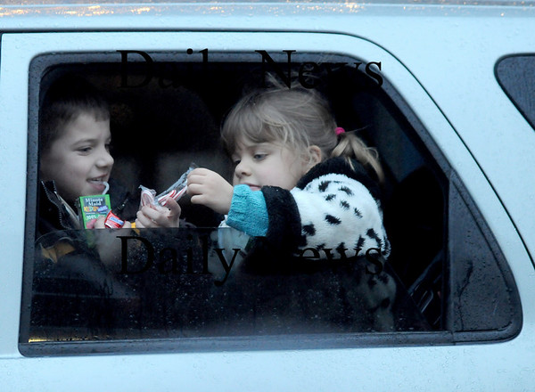 Amesbury: Liam McCarthy, 6, and his sister Megan , 4, of Haverhill share candy canes as the stay dry in their family car at the annual Santa Parade. Jim vaiknoras/Staff photo