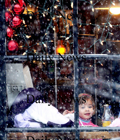 Newburyport:Emily Alford, 4, enjoys her lunch with her mom Tracy in the window of Abraham's Bagels on Liberty Street in Newburyport Thursday as the snow begins to fall.Jim Vaiknoras/Staff photo
