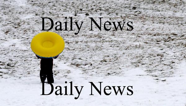 Amesbury: Will Martins, 9, carries his tube back up the hill while sledding at Amesbury Park Saturday morning. Jim Vaiknoras/Staff photo