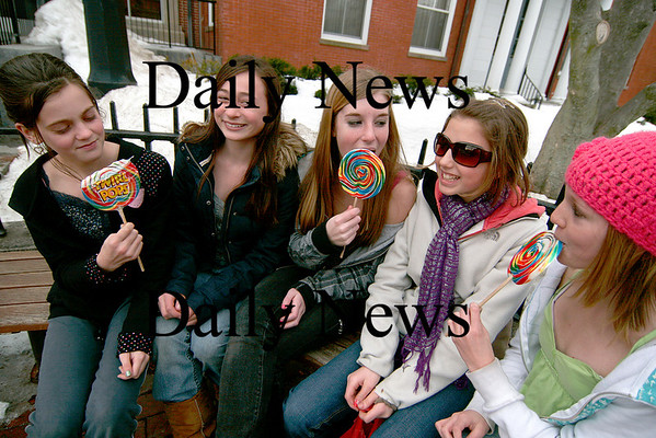 Newburyport: Julia Shorter (right) and her friends Lizzy Kerry, Bryn Willingham, Reins Cracknell, Poppy Gilbault (left) enjoy the warm weather and their half day of school by spending it in downtown Newburyport. Here they eat their candy while waiting outside the Newburyport Public Library. Photo by Ben Laing/Newburyport Daily News Wednesday February 11, 2009.