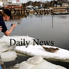 Salisbury:<br /> U.S. Coast Guard Seaman Tatiane Meshoyrer photographs a young harbor seal situated on an ice floe near the Fishtale Diner near Ring's Island in Salisbury. Several people were concerned the mammal may be injured and called the Coast Guard to investigate. <br /> Photo by Bryan Eaton/Newburyport Daily News Wednesday, February 25, 2009