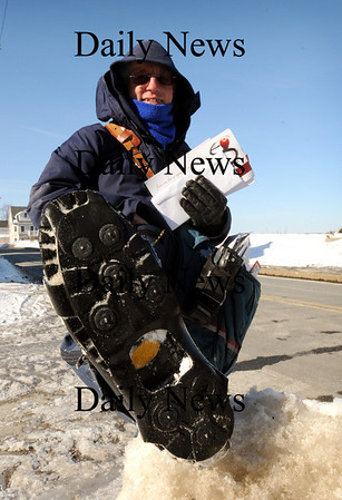 "Newburyport:<br /> Newburyport letter carrier Bill Hinton wears what he calls ""ice cleats"" to deliver mail safely around the icy sidewalks off in the Water Street area.<br /> Photo by Bryan Eaton/Newburyport Daily News Thursday, February 05, 2009"